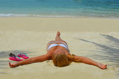 Blond girl suntanning on the beach Stock Photo