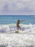 Blond girl surfing the waves Stock Photography