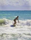 Blond girl surfing the waves Royalty Free Stock Photography