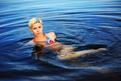 Blond girl swimming in crystal-clear pool. Blond girl in color bikini swimming in crystal-clear pool Royalty Free Stock Photo