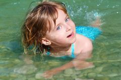 Blond girl swimming in lake river Stock Images