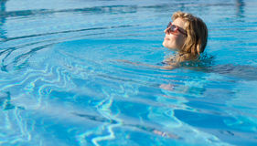 Blond girl swimming in a pool Royalty Free Stock Photo