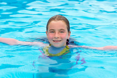 Blond girl swimming in the pool with red cheeks Royalty Free Stock Photography