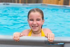 Blond girl swimming in the pool with red cheeks Royalty Free Stock Photos