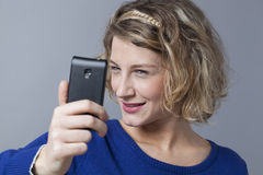 Blond girl taking a cheeky close up selfie Stock Photos
