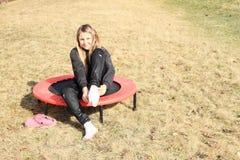Blond girl taking on socks on trampoline Stock Photo