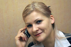 Blond girl talking by phone. And smiling Royalty Free Stock Image