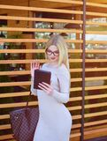 blond girl talking on video call on tablet. An attractive model in sunglasses and a dress uses a tablet royalty free stock image