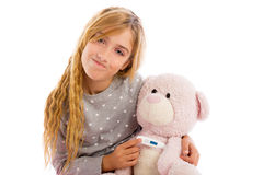 Blond girl with teddy bear thermometer and flu Royalty Free Stock Image