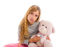 Blond girl with teddy bear thermometer and flu Stock Photo