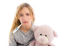 Blond girl with thermometer and flu cold in pyjama. Grumpy face with teddy bear Royalty Free Stock Photography