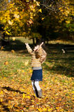 A blond girl throwing up the leaves. Happy girl, lucky and marry, throwing up the tree leaves in the autumn park Royalty Free Stock Photography