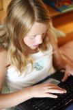 Blond girl tipe on laptop Royalty Free Stock Photography