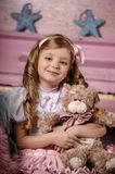 Blond girl with tresses and a teddy bear Stock Photography