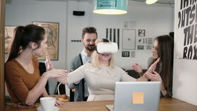 Blond girl tries app for VR helmet virtual reality glasses her friends and colleagues supporting her in modern office stock video