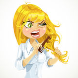 Blond girl unhappy and tries to comb the tangled hair Royalty Free Stock Photos