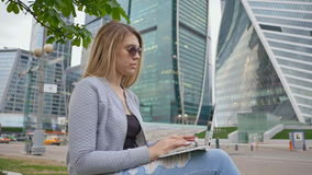 A blond girl uses a white laptop against a background of the city center and tall buildings. Girl in sunglasses. A blond girl uses a white laptop against a stock video footage