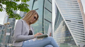 A blond girl uses a white laptop against a background of the city center and tall buildings. Girl in sunglasses. A blond girl uses a white laptop against a stock video