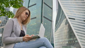 A blond girl uses a white laptop against a background of the city center and tall buildings. Girl in sunglasses. A blond girl uses a white laptop against a stock footage