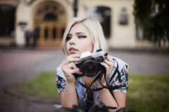 Blond girl with a vintage camera making selfie stock photo