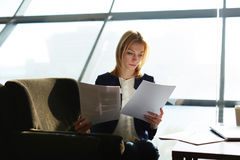 Blond girl waiting conference in the hall. Portrait of attractive businesswoman reading papers or documents sitting in luxury coffee shop next to the window stock photography