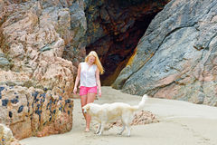Blond girl walking with dog on the beach Stock Images