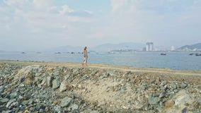Blond Girl Walks on Long Dike in Ocean against Resort City. Blond long haired girl walks on ground dike stretching in tranquil ocean against fishing boats and stock video footage