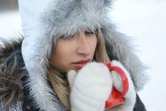 A blond girl in a warm hat is drinking hot coffee Stock Images