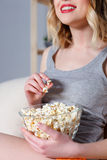 Blond girl watching tv with food Royalty Free Stock Images