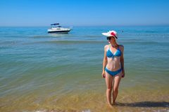 A blond girl wearing sunglasses and a white hat is standing on the beach opposite the yacht. stock photo
