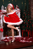 Blond girl wears Santa costume,posing beside Christmas tree and chimney. Fashion interior photo of beautiful young woman with blond hair and charming smile Stock Images