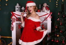 Blond girl wears Santa costume,posing beside Christmas tree and chimney. Fashion interior photo of beautiful young woman with blond hair and charming smile Royalty Free Stock Images