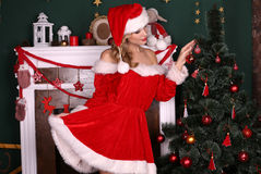Blond girl wears Santa costume,posing beside Christmas tree and chimney. Fashion interior photo of beautiful young woman with blond hair and charming smile Royalty Free Stock Image