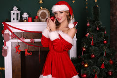 Blond girl wears Santa costume,posing beside Christmas tree and chimney. Fashion interior photo of beautiful young woman with blond hair and charming smile Stock Photo