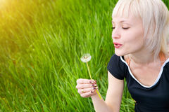 Blond girl with white dandelion Stock Images