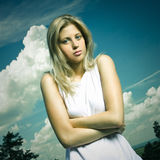 Blond girl in white shirt outdoor. Blue dramatic sky Stock Photography