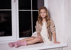 Blond girl on windowsill Royalty Free Stock Image