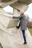 Blond girl in winter coat climbing Stock Images