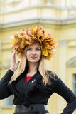 Blond girl in a wreath of  maple leaves Royalty Free Stock Image