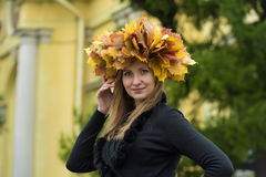 Blond girl in a wreath of  maple leaves Stock Images