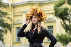 Blond girl in a wreath of  maple leaves Royalty Free Stock Photo