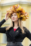 Blond girl in a wreath of  maple leaves Royalty Free Stock Images