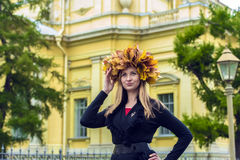Blond girl in a wreath of  maple leaves Royalty Free Stock Photos