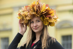 Blond girl in a wreath of  maple leaves Stock Photo