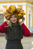 Blond girl in a wreath of  maple leaves Stock Photos