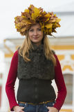 Blond girl in a wreath of  maple leaves Stock Image