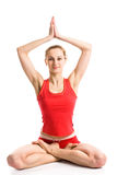 Blond girl  in yoga pose. A pretty blond girl in red underwear sitting in yoga pose with her hands up Royalty Free Stock Images