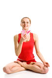 Blond girl in yoga pose. A smiling pretty blond girl in red underwear with a rosy lily sitting  in yoga pose Royalty Free Stock Image
