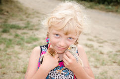 Blond girl with young ducks stock image