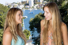 Blond girlfriends chatting. On the balcony with water views stock photo